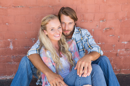 sitting on the ground: Attractive couple sitting on ground on a sunny day in the city Stock Photo