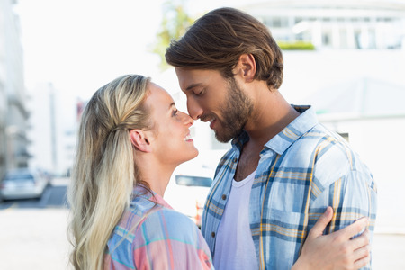 fashionable couple: Attractive couple standing and hugging on a sunny day in the city Stock Photo
