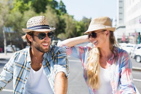 gafas de sol: Feliz pareja atractiva con gafas de sol en un d�a soleado en la ciudad