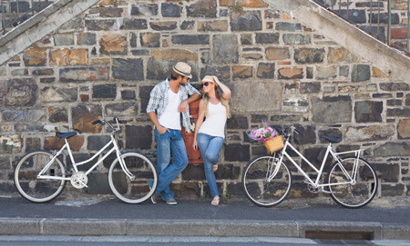 fashionable couple: Attractive couple standing with bikes on a sunny day in the city