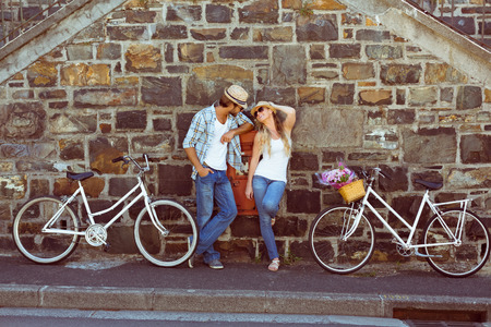 city life: Attractive couple standing with bikes on a sunny day in the city