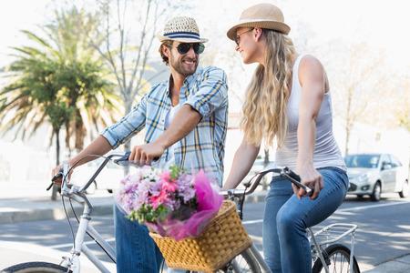 urban style: Atractiva pareja en un paseo en bicicleta en un d�a soleado en la ciudad Foto de archivo