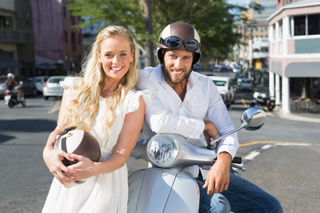 crash helmet: Attractive couple with their scooter on a sunny day in the city Stock Photo