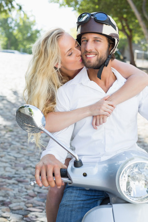 Attractive couple with their scooter on a sunny day in the city Stock Photo