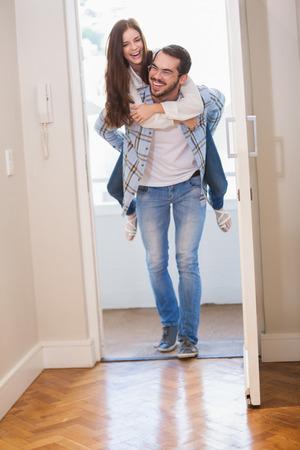 Jeune homme donnant copine un tour de ferroutage dans leur nouvelle maison Banque d'images