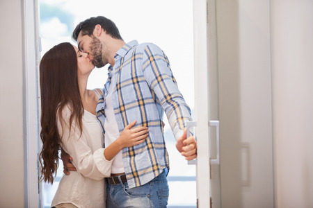 young couple hugging kissing: Young couple kiss as they open front door in their new home