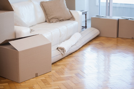 moving up: Rolled up carpet and boxes in a new house