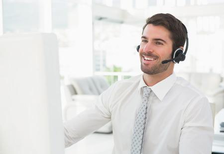 centro de computo: Hombre de negocios sonriente con auriculares interactuando en su oficina