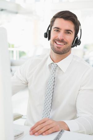 computer centre: Hombre de negocios feliz con auriculares interactuando en su oficina