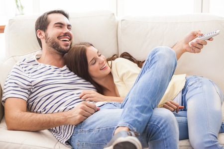 living: Cute couple relaxing on couch at home in the living room