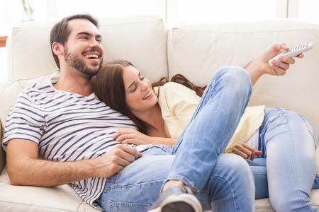 personas viendo television: Linda pareja relajarse en el sof� en casa en la sala de estar