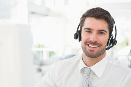 Handsome businessman with headset interacting in his office Banco de Imagens