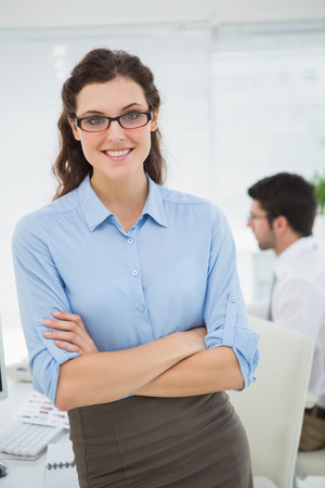 Smiling businesswoman with arms crossed in the office