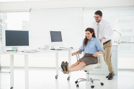 sillon: Personas felices jugando junto con la silla giratoria en la oficina