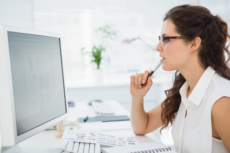 computer monitor: Focused businesswoman with glasses using computer in the office