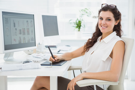 digitizer: Smiling businesswoman using digitizer at desk in the office