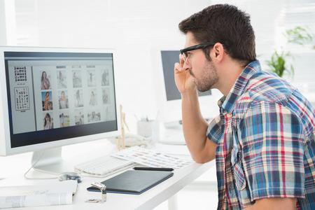 オフィスのコンピューターのモニターを使用して焦点を当てた実業家
