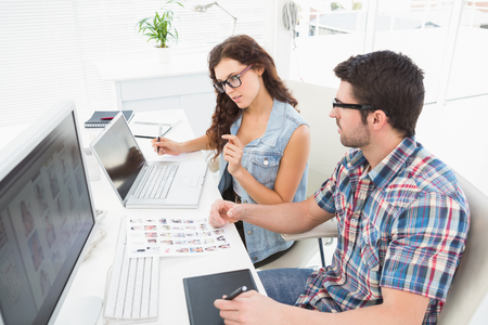 digitizer: Concentrated coworkers using laptop and digitizer in the office Stock Photo