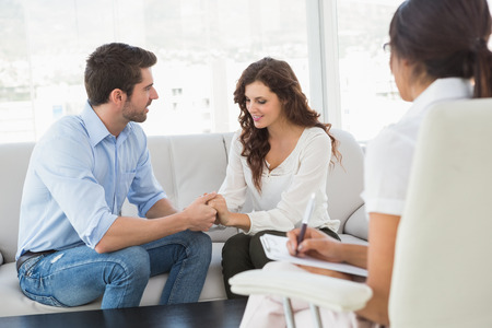 therapist: Reconciled couple smiling at each other in the therapist office Stock Photo