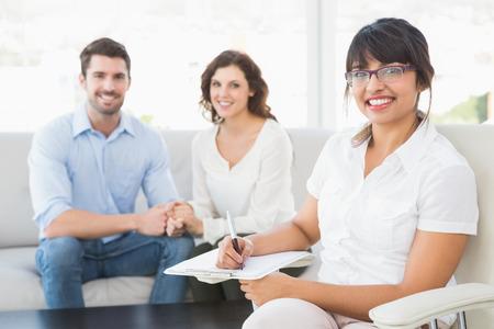 Terapeuta sonriente con los pacientes que mira la cámara en la oficina