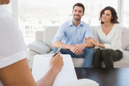 Reconciled couple smiling and talking with their therapist in the office
