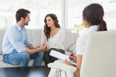 couples therapy: Reconciled couple smiling at each other in the therapist office Stock Photo