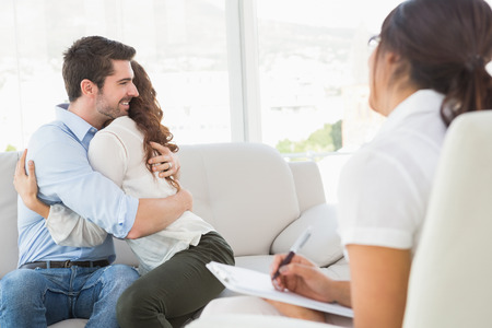 marriage counseling: Smiling couple hugging in front of their therapist in the office Stock Photo