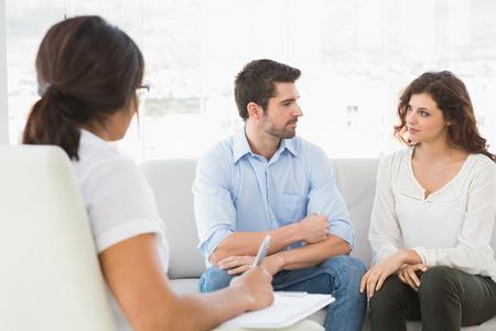 matrimonio feliz: Pareja sentada en el sofá hablando con su terapeuta en la oficina