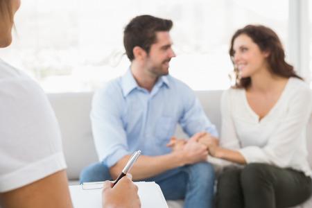 matrimonio feliz: Reconciliados pareja sonriendo el uno al otro en la oficina terapeuta Foto de archivo