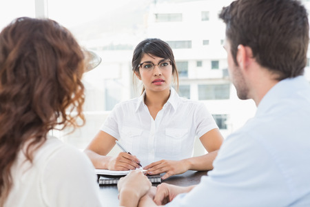marriage counseling: Therapist listening her patients and taking notes in the office
