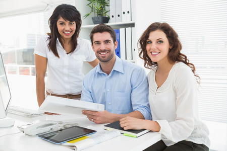 happy business team: Smiling coworkers working together at desk in the office Stock Photo