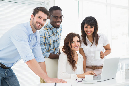 professional portrait: Happy coworkers working together with laptop in the office