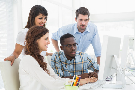business casual: Concentrated coworkers using computer together in the office Stock Photo