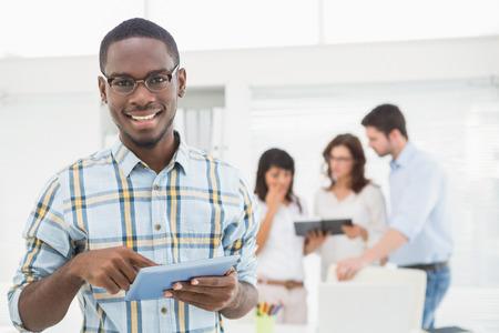 hombres negros: Hombre sonriente que usa la tablilla delante de sus colegas en la oficina
