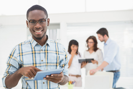 black business man: Smiling man using tablet in front of his colleagues in the office Stock Photo