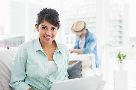 obreros trabajando: Empresaria alegre en el sof� mirando a la c�mara en la oficina