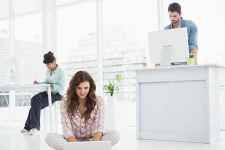 Cheerful businesswoman sitting on the floor using laptop with colleagues behind her Stock Photo