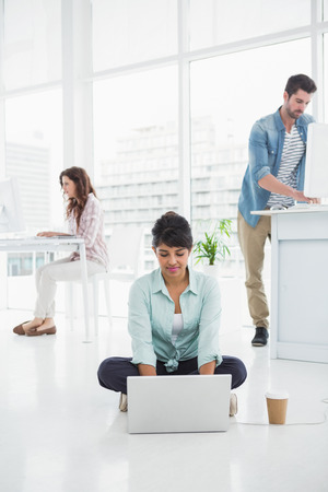 attractive office: Casual businesswoman sitting on the floor using laptop with colleagues behind her