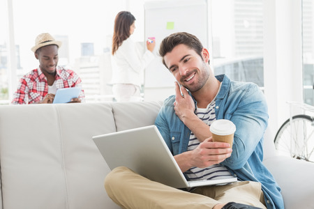 Businessman phoning and holding laptop on sofa in front of his colleagues in the office Stock Photo