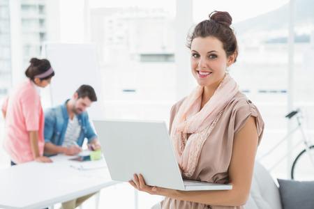 그녀의 뒤에 동료들과 함께 서 노트북을 사용하는 젊은 사업가 스톡 콘텐츠