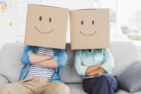 cara sonriente: Compa�eros de trabajo con la cara sonriente en el sof� en la oficina Foto de archivo