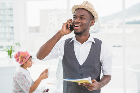 cool guy: Smiling businessman phoning and holding notebook in the office