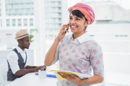 Smiling businesswoman phoning and holding notebook in the office