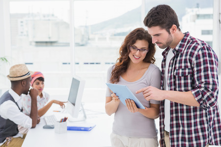 Coworkers standing and using tablet together with colleagues behind them photo