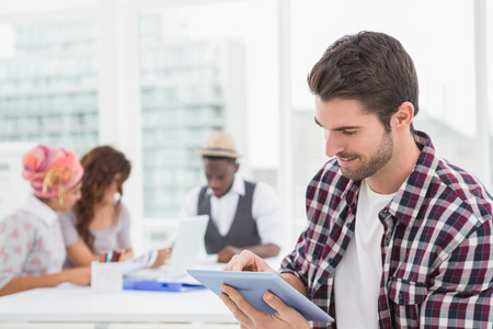 Casual businessman using digital tablet with colleagues behind him photo