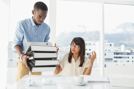 exasperated: Man giving pile of files to his exasperated colleague in the office