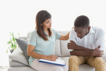 Therapist reassuring her upset patient at therapy session Stock Photo