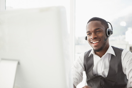 persona alegre: Hombre de negocios sonriente con auriculares interactuando en su oficina