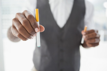 man smoking: Businessman holding electronic cigarette and cigarette in the office