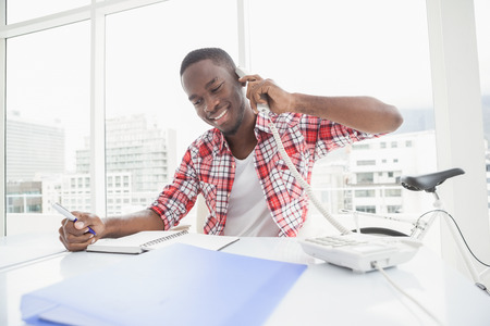 phoning: Happy businessman phoning and taking notes in the office